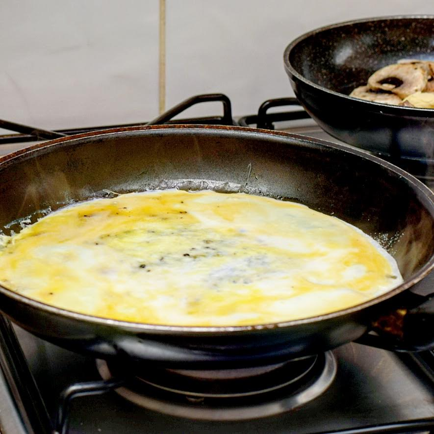 Omelette cooking in a  frying pan