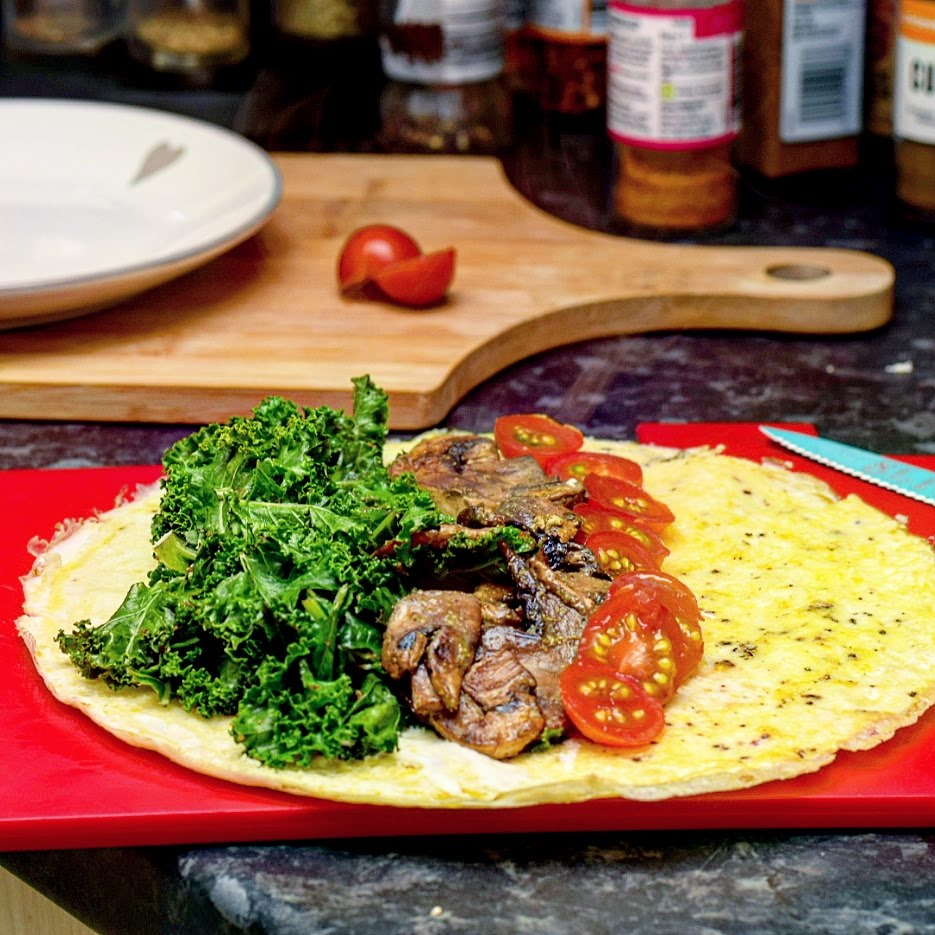 Omelette as a wrap, topped with mushroom, kale and tomato