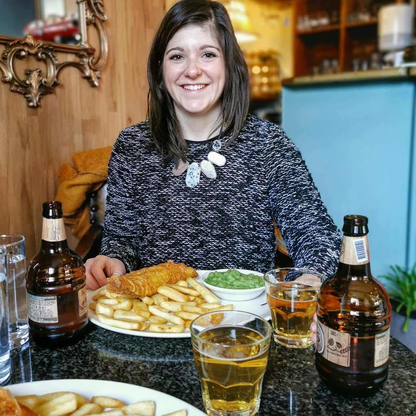 female at table with plate of fish and chips with mushy peas, and beer in front