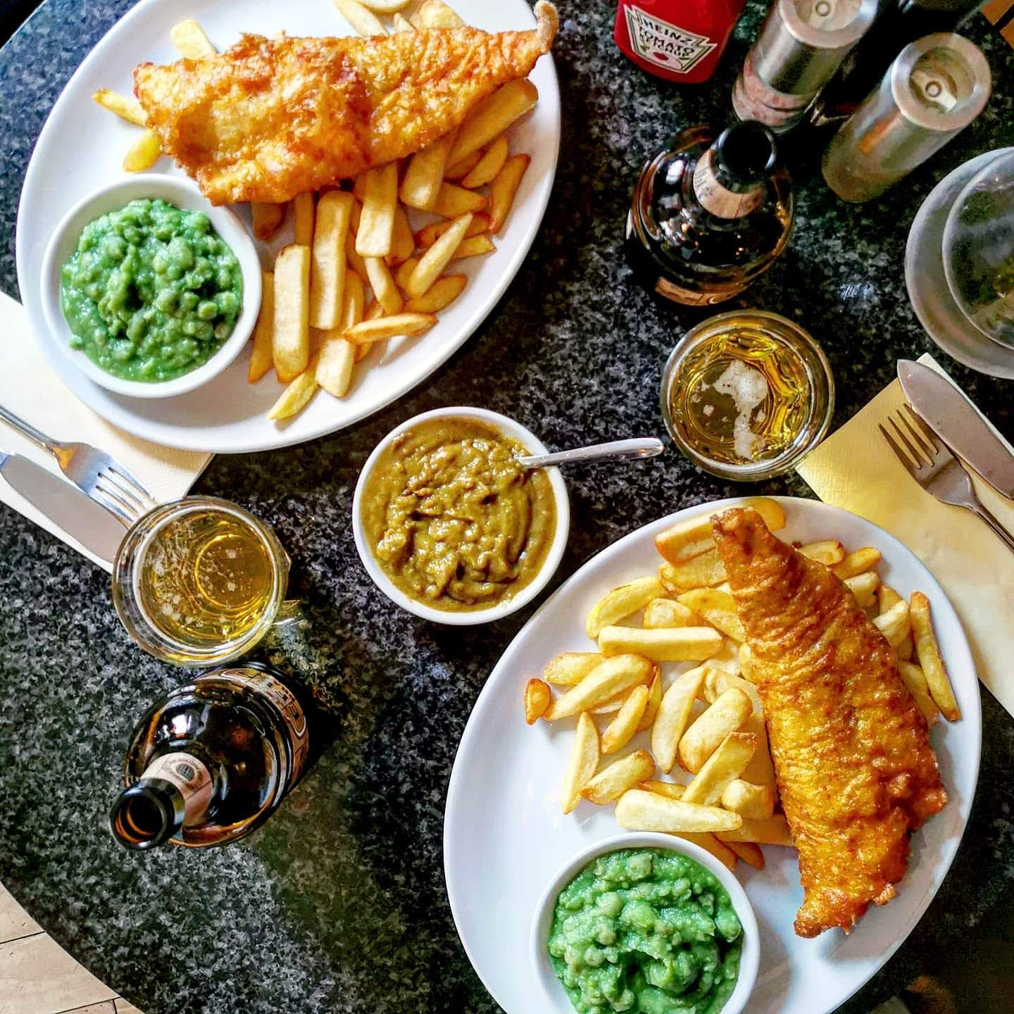 Overhead view of two plates of fish and chips with mushy peas, a side of curry sauce and two beers