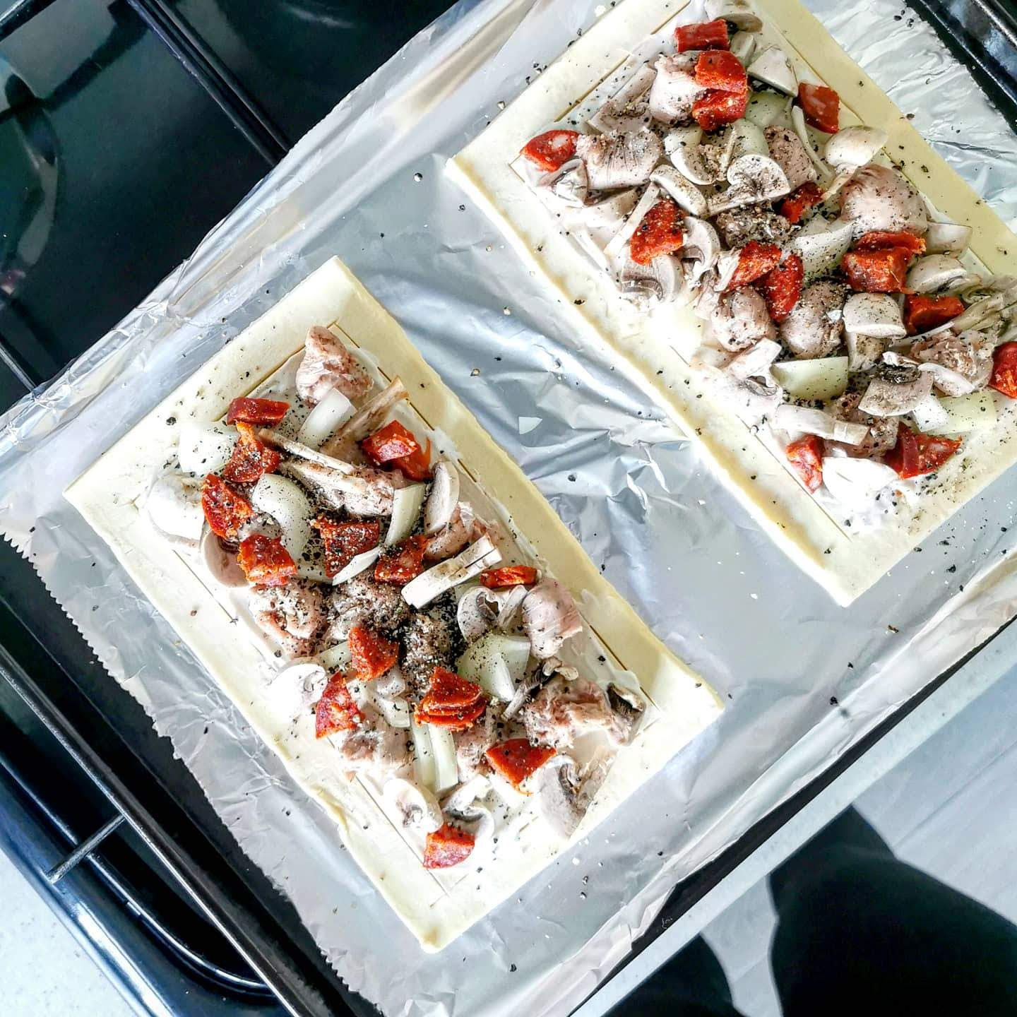 Puff pastry topped with sausage, chorizo, onion and mushroom before cooking, on a tray with tin foil