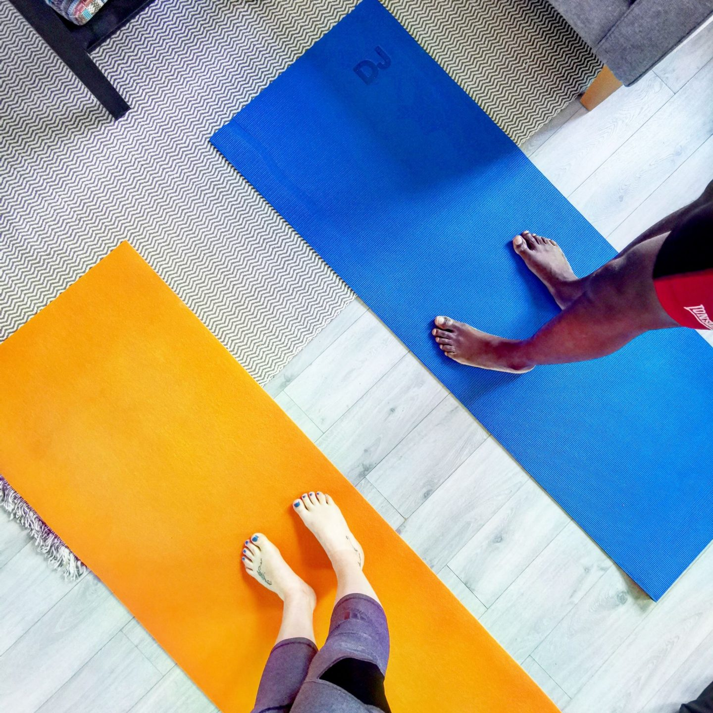 Two people standing on fitenss mats ready for home workouts
