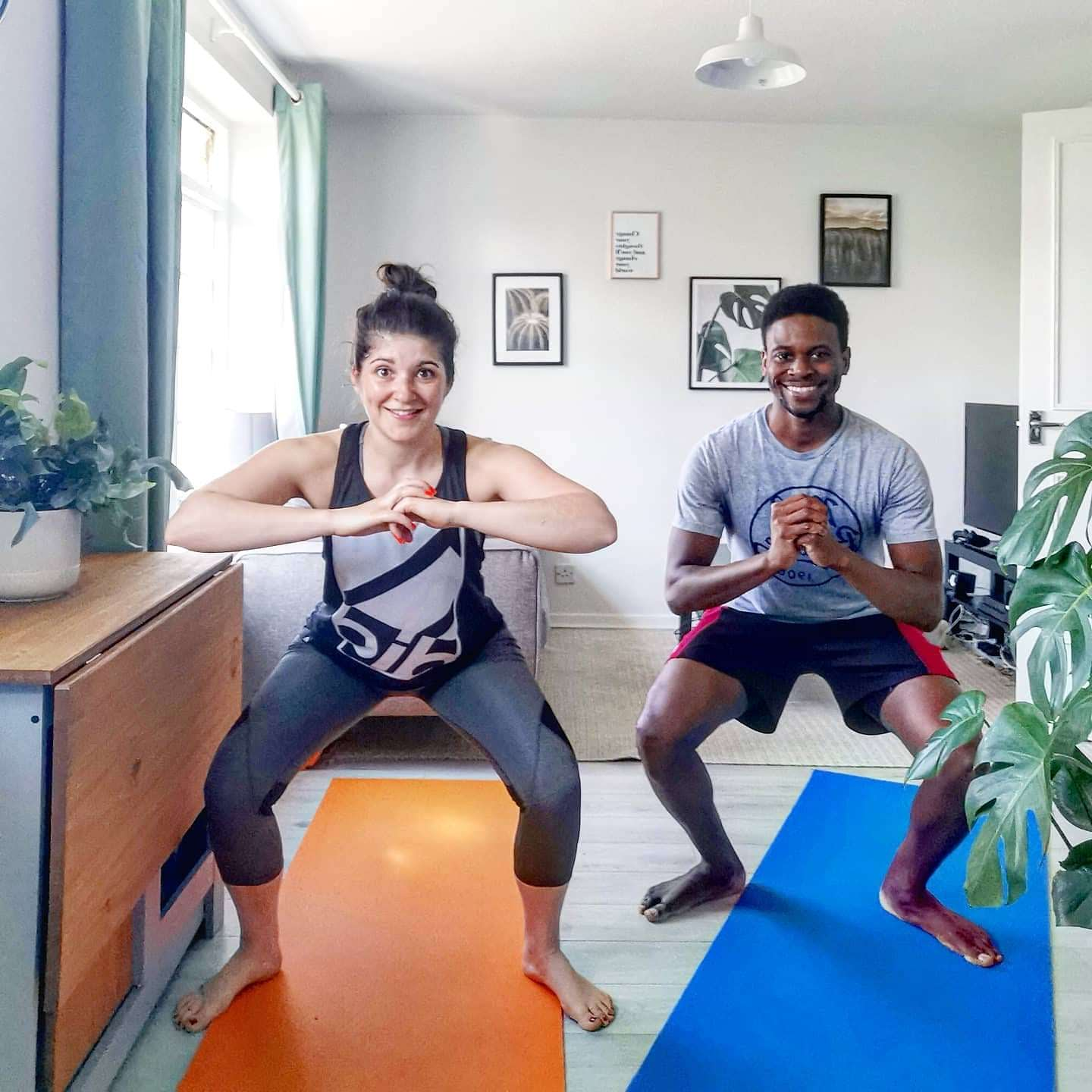 Two people squatting during home workouts