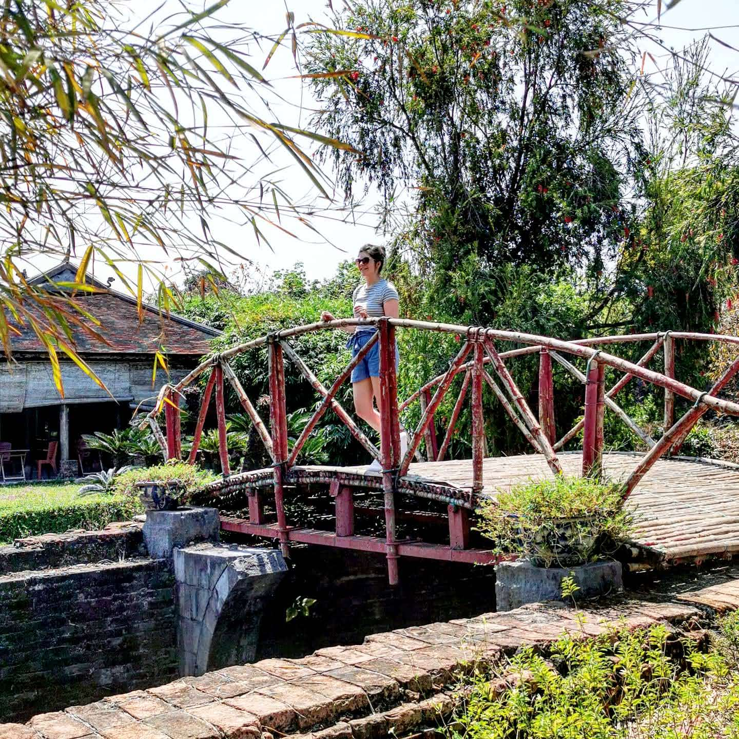 Woman stood on bridge in gardens in Imperial City of Hue